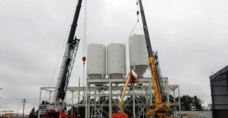 Bulk storage silos being put on a structure for a paving plant.