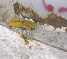 Corrosion of cylinder wall above external horizontal flange due to material buildup that trapped moisture