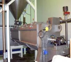 Continuous ribbon mixer used for combining raw dry and wet ingredients before extruder