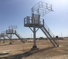 A solution for a frac-sand truck station. The solution includes a stationary galvanized platform with a wide spring balanced aluminum safety bridge with safety enclosure/cage making it easier to raise and lower the gangway while accessing the tops of the bulk truck.