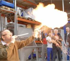 """Swiss expert Dr. Glor demonstrating that """"the long duration of the flame compared to a gas explosion makes dust explosions particularly dangerous"""" during a recent seminar at a leading vacuum conveyor company seminar in Soest, Germany."""