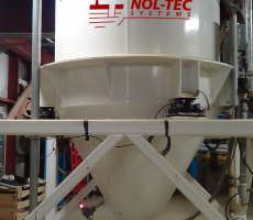 A pneumatic conveying transporter allows for gravity-driven separation of material from motive air and dust.